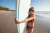 'A woman holds her surfboard on playa santa teresa (santa teresa beach) in santa teresa and mal pais (malpais) on the nicoya peninsula;Puntarenas province costa rica'