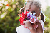 'A young girl smelling a colourful bouquet of flowers;Torremolinos malaga spain'