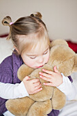 'A Young Girl With Down Syndrome Cuddles With Her Teddy Bear; Cambridge, England'