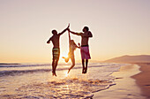 'Three people leaping in the air to clap hands together on a beach at sunset;Tarifa cadiz andalusia spain'