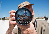 'A man holds a camera with a reflection of a young woman sitting on a horse in the lens;Mijas malaga andalusia spain'