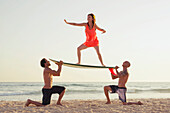 'Two men hold a surfboard as a woman stands on it in a surfer pose;Tarifa cadiz andalusia spain'