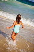 'A young girl runs in the ocean from the beach;Gold coast queensland australia'