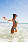 'A young woman in a bikini splashes water as she stands in the ocean;Gold coast queensland australia'
