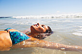 'A young woman lays in the shallow water off the beach;Gold coast queensland australia'