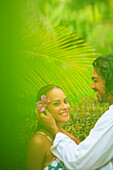 'A man puts a flower in a woman's hair at the bora bora nui resort and spa;Bora bora island society islands french polynesia south pacific'