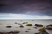 'Rocks in tranquil water under storm clouds;Northumberland england'