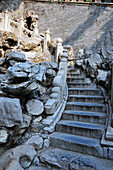 'Pile of rocks beside steps and a railing;Beijing china'