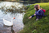 'A young girl feeds a bird at the water's edge;Currumbin valley gold coast queensland australia'
