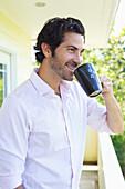'A man drinking a cup of coffee on a balcony;Wailua kauai hawaii united states of america'