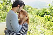 'A man and woman in an embrace as he kisses her forehead;Wailua kauai hawaii united states of america'