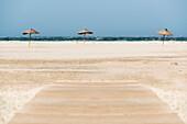 'Three umbrellas on a white sand beach along the water's edge;Tarifa cadiz andalusia spain'