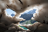 'Underneath a melting snow pack with gaps showing mountains and lake with blue sky in kananaskis provincial park;Alberta canada'