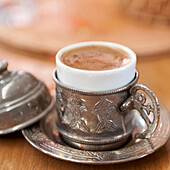'Hot beverage with foam served in a silver cup and saucer set;Istanbul turkey'