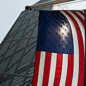 'American flag hanging with a building in the background;Chicago illinois united states of america'