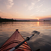 'Bow of a red kayak and paddle on a tranquil lake at sunset;Keewatin ontario canada'