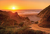 'Orange california sunset on the ocean with trail down to a beach;California united states of america'