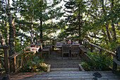 'A table set for a meal on a wooden deck surrounded by trees by a lake;Lake of the woods ontario canada'