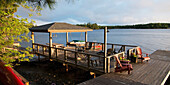 'Patio furniture on a wooden dock on a lake;Lake of the woods ontario canada'