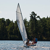 'Three teenagers on a sailboat in a lake;Kenora ontario canada'