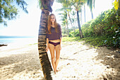 'A young woman poses beside a palm tree on a beach;Kauai hawaii united states of america'