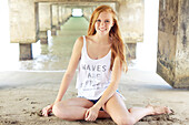 'A young woman with long red hair sits in the sand under a bridge at the water's edge;Kauai hawaii united states of america'