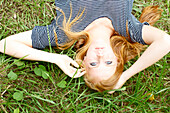 'A young woman with long red hair laying in the grass;Kauai hawaii united states of america'
