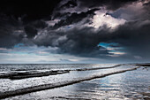 'Dark storm clouds over the ocean with waves rolling into the shore;Druridge bay northumberland england'