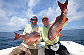 'Two men hold just caught mullet snappers; panama'