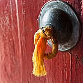 'Gold tassel tied to a doorknob on a red door;Lhasa xizang china'