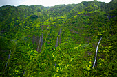 'Waterfalls flowing down the mountains covered with lush green trees;Hawaii united states of america'