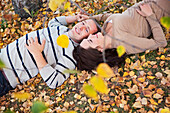 'A couple laying in the fallen leaves in autumn;St albert alberta canada'