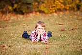'Portrait of a young boy laying in the grass in a park in autumn;Edmonton, alberta, canada'