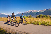 'Two women and a man biking on the bird point to girdwood bike trail, turnagain arm;Anchorage, alaska, united states of america'