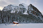 'A snow covered log cabin on a lakeshore with lights at dusk surrounded by snow covered evergreen trees and mountains;Lake louise alberta canada'