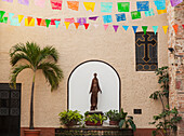 'A sculpture of san francisco de assisi is sheltered by the church of our lady of guadalupe;Puerto vallarta mexico'