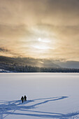 Sillhouetted Ice Fisherman On Summit Lake, Clouds Clearing From The Kenai Mountains Behind The Lake, Chugach National Forest, Backlit Sun, Winter, Southcentral Alaska, Usa.