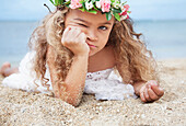 'Portrait of a cute young girl laying on beach making a face;Waikiki oahu hawaii united states of america'