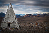 'A stone conical structure on a barren landscape with mountains in the background;Tibet'