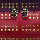 Red doors with round gold decorative pieces and door knockers in animal likeness