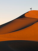 A person stands on a top ridge of a sand slope