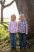 'Two young girls with blond hair hold hands standing in front of a large tree trunk;Crab cove california united states of america'