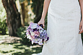 A bride stands holding her bouquet