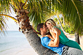 'A couple lays on the trunk of a palm tree at the water's edge; Honolulu, Hawaii, United States of America'