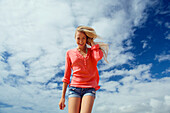 'Portrait of a teenage girl with long blond hair against a blue sky and cloud; Kauai, Hawaii, United States of America'