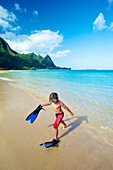 'A boy on the beach with snorkelling gear; Kauai, Hawaii, United States of America'