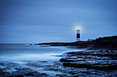 'Waves breaking on the Inis Oirr shoreline over looked by the Inis Oirr Lighthouse; Aran Islands, Ireland'