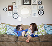 'Brother and sister sitting on a couch at home; Victoria, British Columbia, Canada'