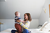 'A sister playing with her baby brother on a bed at home; Victoria, British Columbia, Canada'
