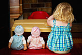 'A toddler sits at a play table with her two dolls; Alberta, Canada'